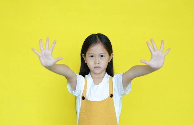 Little girl doing stop sing with two palm of hands on yellow background