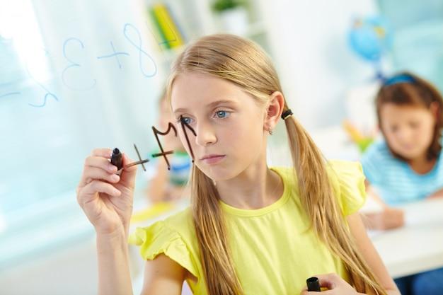 Маленькая девочка делает сумму с одноклассниками на фоне