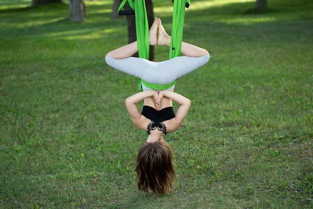 Маленькая девочка делает упражнения йоги с гамаком в парке