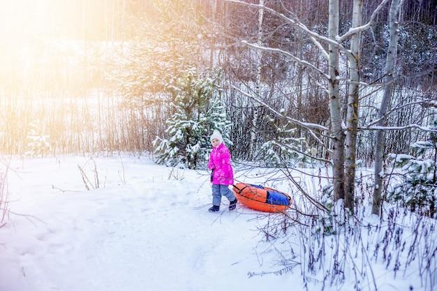 小さな女の子がスライドスライドチーズケーキを雪の丘の上にドラッグします。子供のための冬の野外活動の概念。