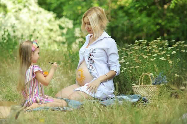 小さな女の子は、公園の屋外で、妊娠中の母親の胃に太陽を描きます