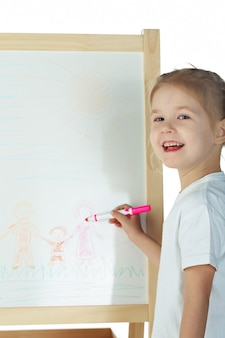 Маленькая девочка рисует на белом столе