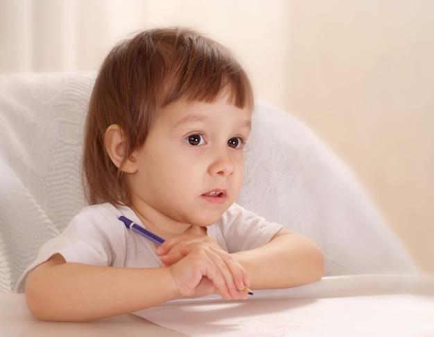 Маленькая девочка рисует дома за столом