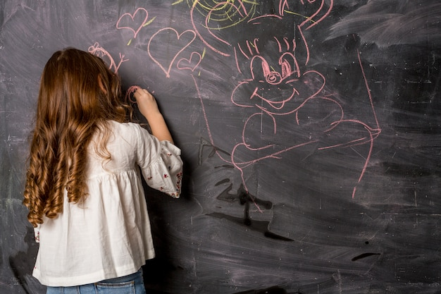 Little girl drawing on blackboard
