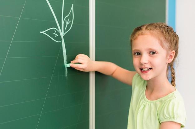 Little girl drawing on the blackboard