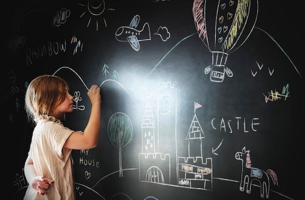 Little girl drawing on a blackboard