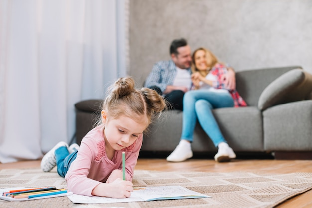Little girl drawing on book lying floor while her loving parents sitting on sofa