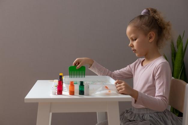 墨流しのテクニックを描き、さまざまなツールを使用して小さな女の子