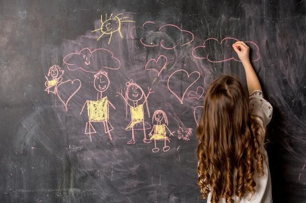 Little girl drawing family on blackboard