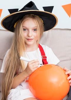 Little girl drawing a halloween baloon