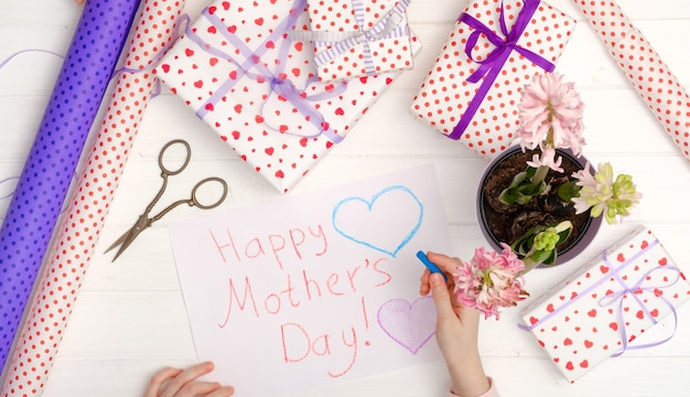 Little girl drawing happy mother's day greeting card with presents on the table. mothers day background