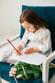 Little girl drawing heart on paper sheet