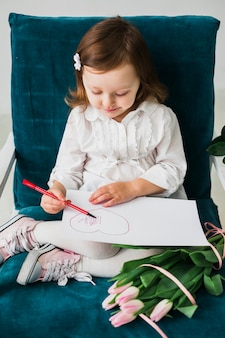Little girl drawing heart on paper