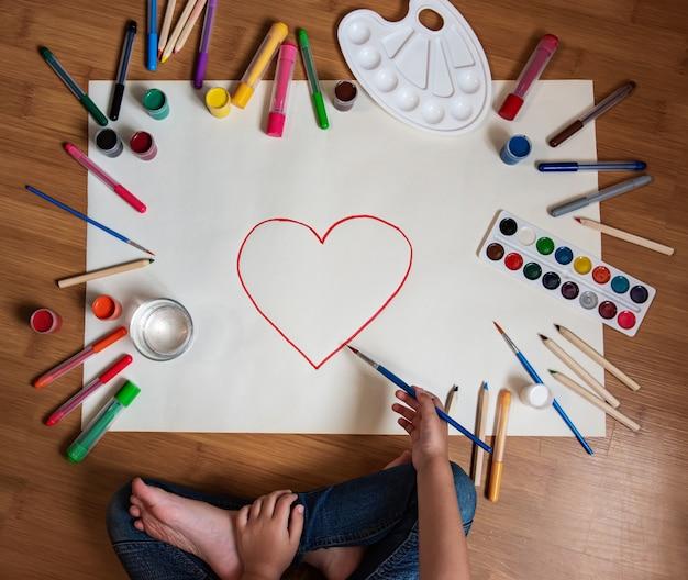 Little girl drawing heart in paper