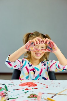 Little girl, drawing at home and make heart from hands