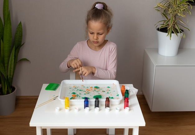 テーブルに座って、墨流しのテクニックで描く少女。墨流しアート