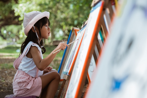 Маленькая девочка, рисование в парке