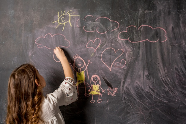 Little girl drawing mother and daughter on blackboard