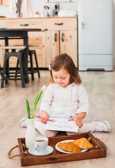 Little girl drawing near tray with coffee