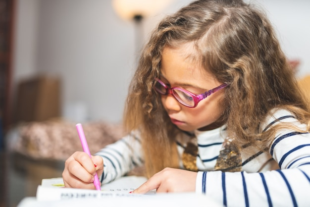Little girl drawing on a notebook