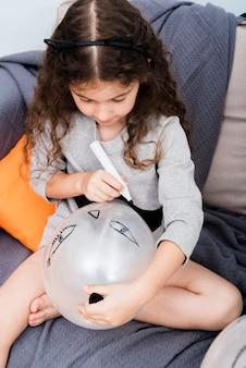 Маленькая девочка, рисование на воздушном шаре на хэллоуин