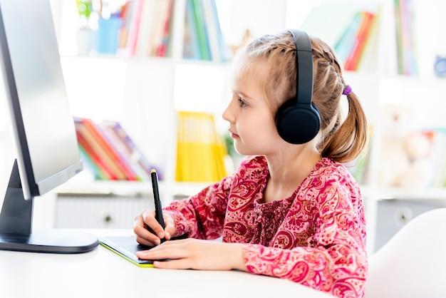 Маленькая девочка рисует на графическом планшете перед компьютером во время онлайн-урока