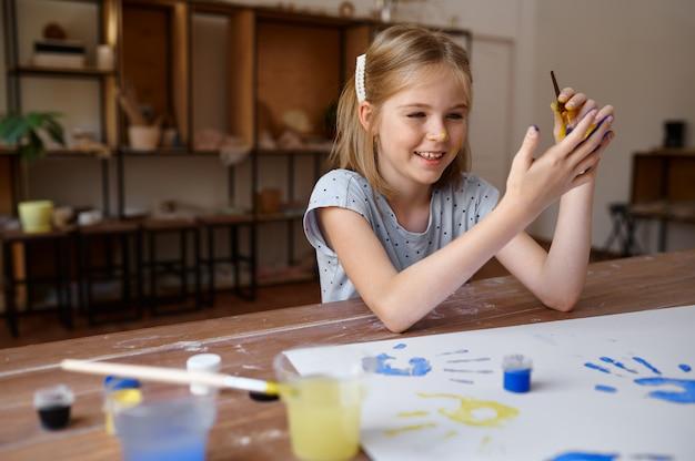Маленькая девочка, опираясь на руки, ребенок в мастерской