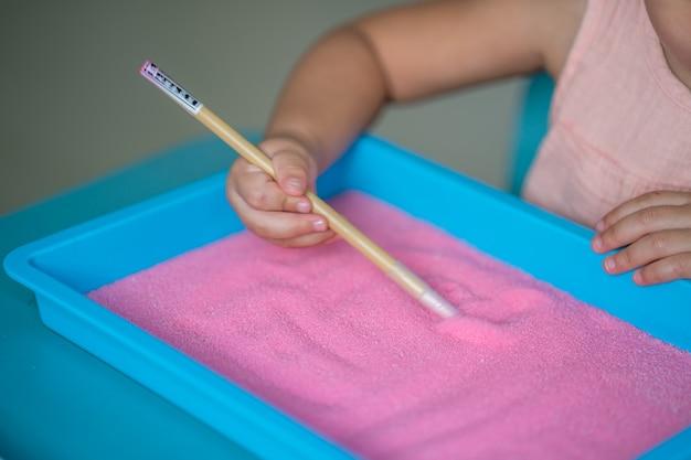 屋内でピンクの砂に描く少女