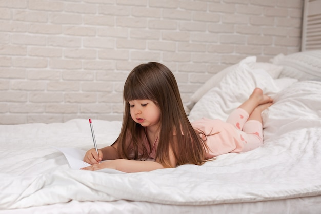 Little girl drawing pictures while lying on bed.