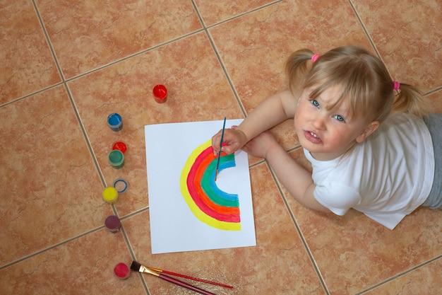 Little girl drawing rainbow. quarantine fun. kids paint.