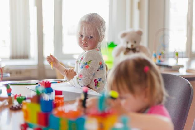 Маленькая девочка, сидя за столом