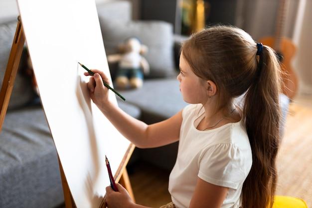 Little girl drawing using easel