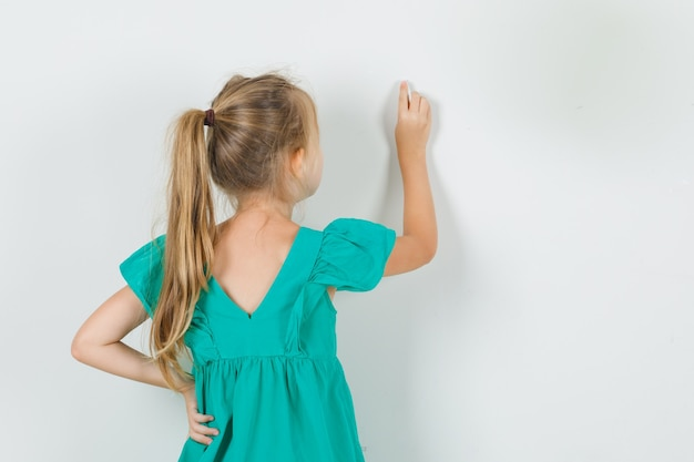 Little girl drawing on wall with finger in green dress back view.