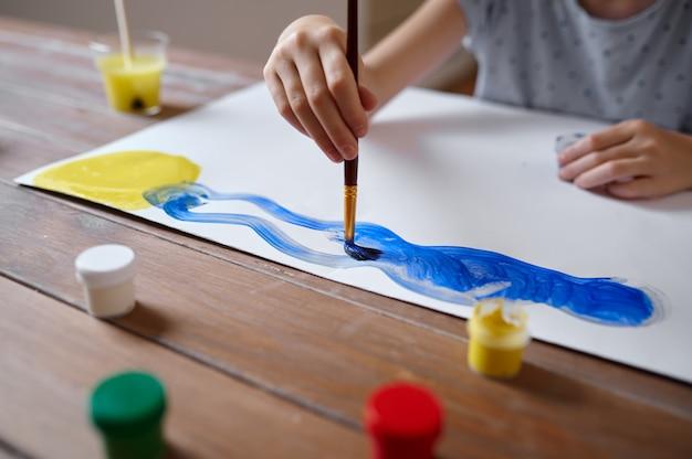 Маленькая девочка рисунок кистью и гуашью за столом, ребенок в мастерской. урок в художественной школе. молодой художник, приятное хобби, счастливое детство