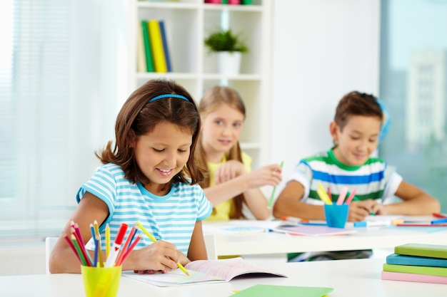 Little girl drawing with classmates on background Free Photo