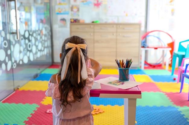 Маленькая девочка, рисование цветной ручкой в бумаге на столе в игровой комнате, концепция здорового ребенка и дошкольного образования
