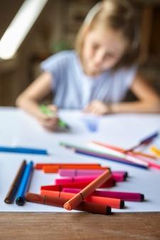 Маленькая девочка рисунок с маркерами за столом, ребенок в мастерской. урок в художественной школе. молодой художник, приятное хобби, счастливое детство. творческое развитие
