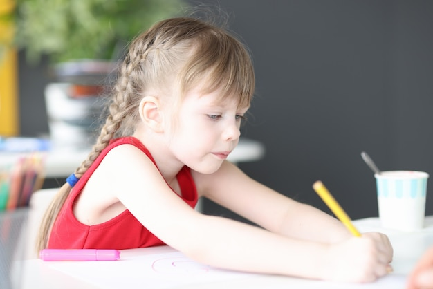 Little girl drawing with multicolored pencils at home