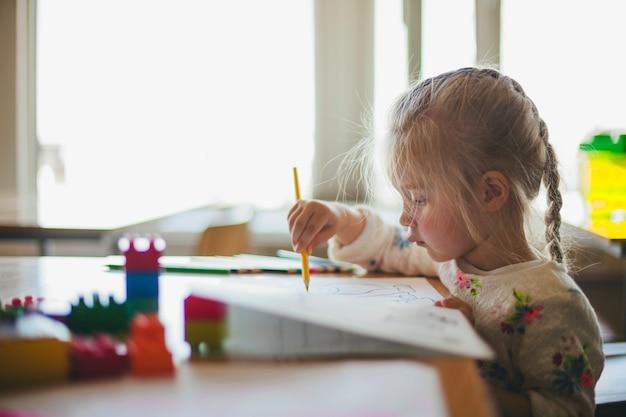 Bambina che disegna con la matita sulla carta