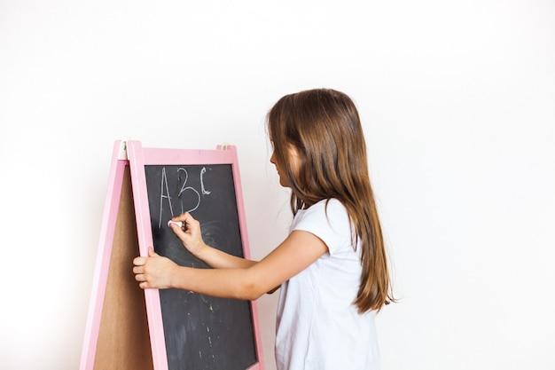 어린 소녀는 분필 보드를 그립니다