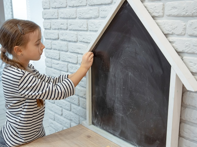 A little girl draws a chalk drawing on a blackboard in the shape of a house.