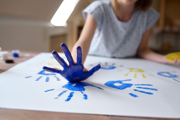Little girl draws a handprint, kid in workshop