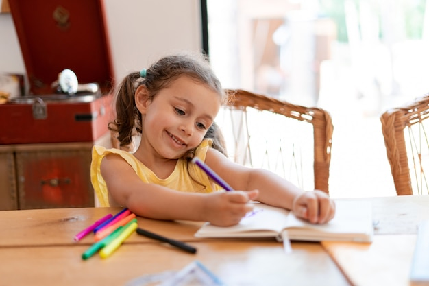A little girl draws in a notebook with colored markers, sitting at a wooden table enjoys her creative process.