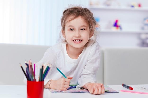 Маленькая девочка рисует, сидя за столом