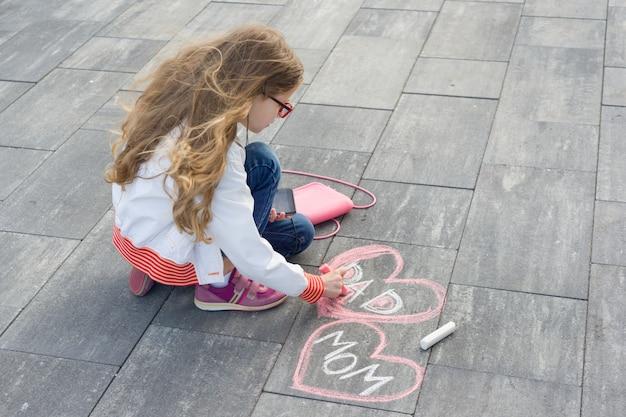 小さな女の子はハートの形でテキストママとパパを描画します