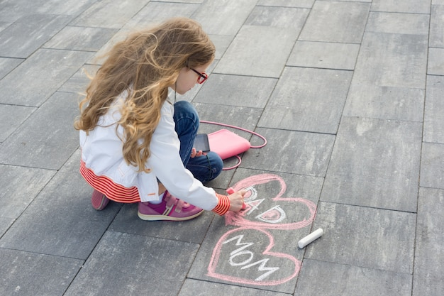 Little girl draws text mom and dad in the shape of heart