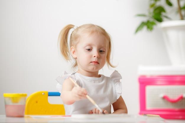 Маленькая девочка рисует акварели, находясь дома в своей комнате. ребенок занимается творчеством. маленький художник.
