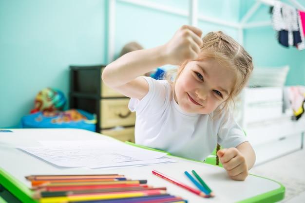 Маленькая девочка рисует, сидя за столом в комнате на фоне стены