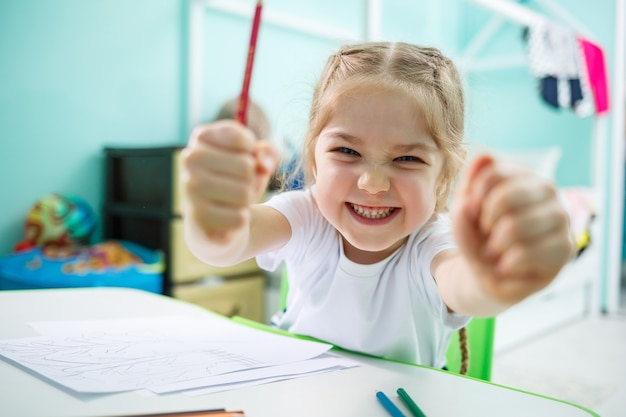 Little girl draws while sitting at a table in a room against the background of the wall