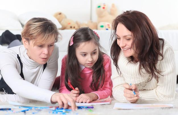 Маленькая девочка рисует с мамой и бабушкой.